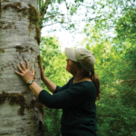 Photo of Sarah Spaeth admiring bear marks on a tree at the Duckabush River. Photo by Jessica Plumb.