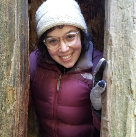 Photo of staff member Lilly Schneider smiling from inside a hollow tree.