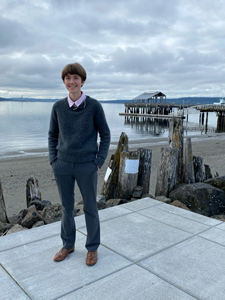 Photo of staff member Tali Hamilton standing beside the beach in downtown Port Townsend.