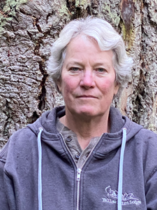 Portrait of a Jane Guiltinan, woman with short grey hair and a purple sweatshirt standing in front of tree so large it fills the frame.