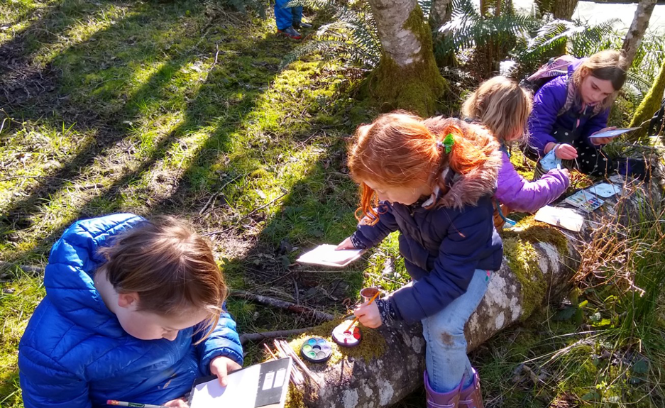 Four children in puffy jackets are doing watercolors on a log in the forest.