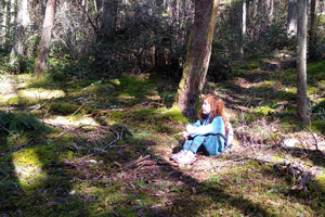 A young red-haired girl sits on sun-dappled moss in the forest.