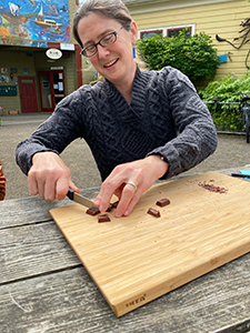 A smiling woman cuts chocolate squares on a cutting board.
