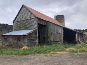 An unpainted wooden barn.