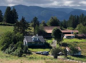 Farm spread before mountains.
