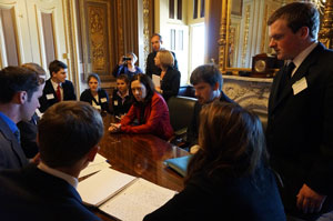Teenagers gathered around a table with Senator Maria Cantwell.