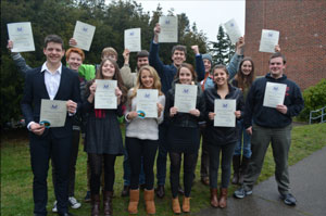 A group of smiling teenagers waving award certificates.