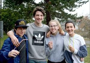 Four smiling teenagers holding drinking straws.