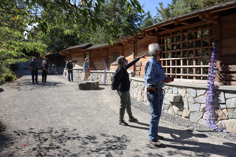 People viewing a stone and wood memorial wall.