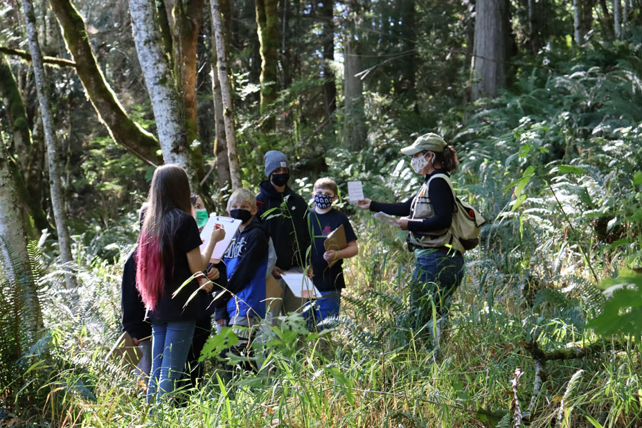 Group of students and an adult huddled in a forest.